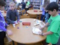 Students build paper ships that are strong enough to support pennies