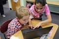 Fourth graders helping second graders use their Chromebooks