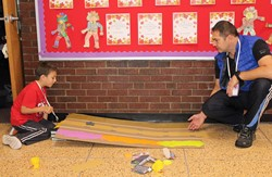 Students test their car's ability to travel down a ramp covered with three different surfaces.
