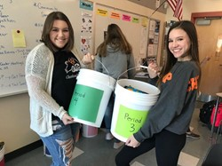 filling buckets full of school supplies for hurricane victims