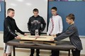 Students test the strength of their structures on the earthquake board