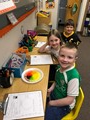 First graders experiment to see what will happen when they pour water on Skittles candies