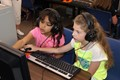 Older students pair up with younger students for work in the Computer Lab