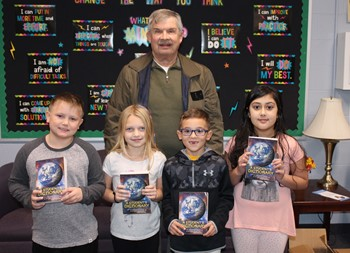 Four third graders with Rotarian Bob Bauer