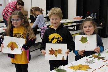 Three students holding their leaf rubbings