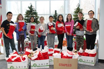 Nine students holding stockings in front of Christmas trees