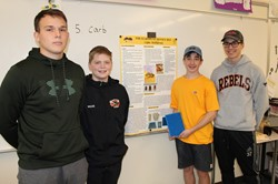 Four students with their bee poster and hive model