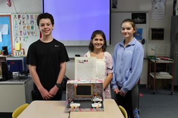 Three students with their presentation materials