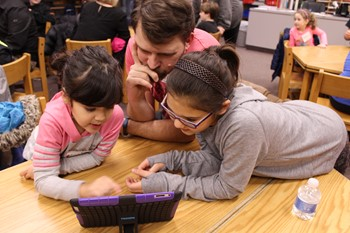 Students and and father working together using an iPad