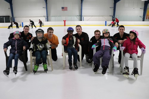 Hockey players and their new friends on the ice