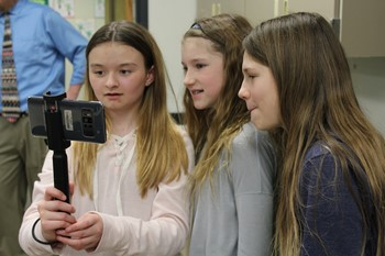 Three students looking at the Google app on a cell phone