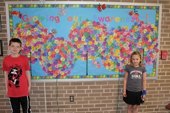 Two students in front of the autism awareness bulletin board