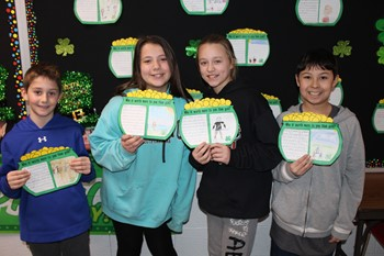 Four students with their pot of gold writing assignment