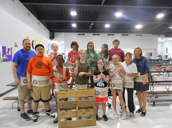 Students modeling their carpenter's aprons and pencils