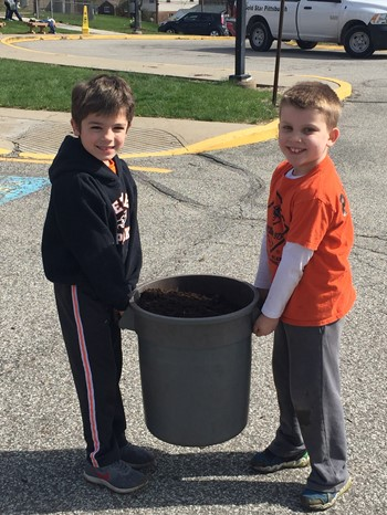 Two students holding a trash can