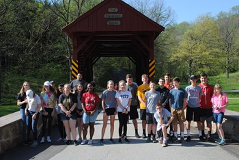 Students in front of a covered bridge.