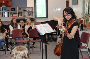 Violinist playing while students look on