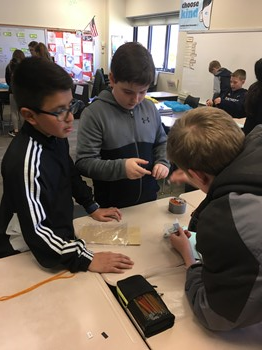 Three students working on the experiment