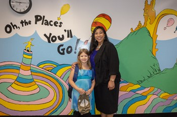 Student and principal by the Dr. Seuss mural