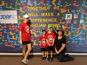 Landen, his mom and his little brother with Mrs. Clifford in front of the JDRF bulletin board
