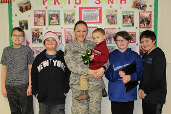 Staff Sgt. Pagano, her son and his toy with four of the five students who purchased the gift.
