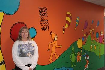 Mrs. Eckert-Graffam in front of the Dr. Seuss wall