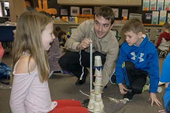 Two students look on as Mr. Schnupp measures the height of their tower
