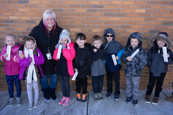 Mrs. Clancy and her students holding up their thermometers