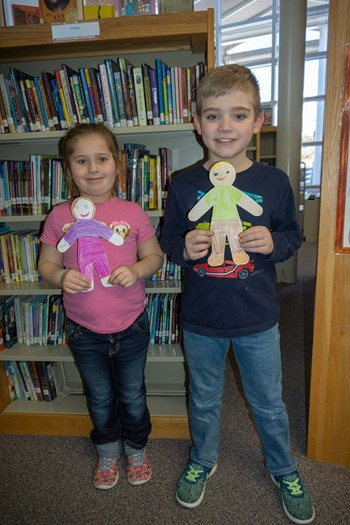 Two students holding paper likenesses of themselves