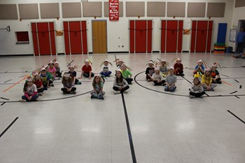"Students sitting on the floor in the shape of ""100"""