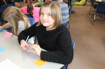Student writing a kind message on a sticky note