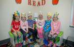 six students wearing crowns