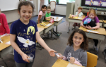 Student giving a Friendship Bracelet to another student