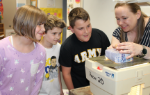Mrs. Meucci showing an egg to three students
