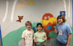 Three students in front of the mural