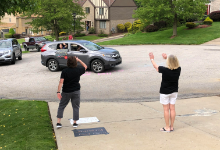 Mrs. DeCarlo and Mrs. Vandewater waving to the cars