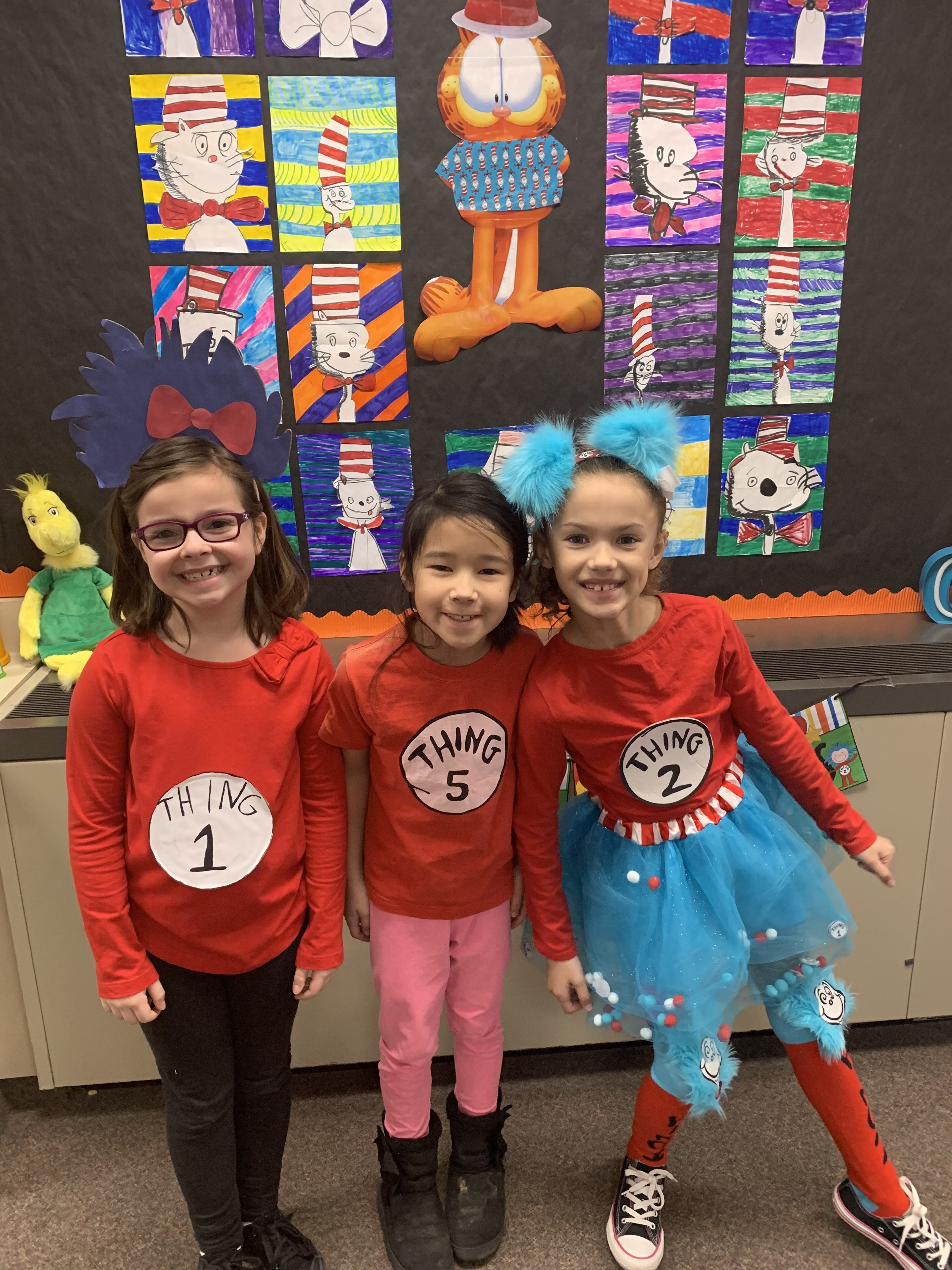 Three students dressed as Thing 1 and Thing 2