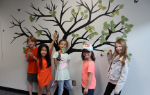 Five students in front of the Kindness Tree