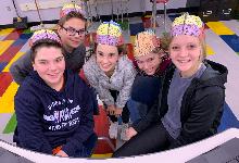 Five students wearing brain hats