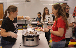 Students putting pancakes on a plate