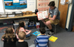 Middle school student reading to a group of elementary students
