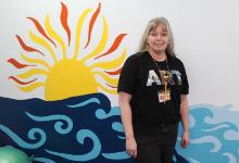 Mrs. Eckert-Graffam in front of the mural