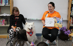 Mrs. Guenther reading a book as Teddy and Mrs. Lewis look on