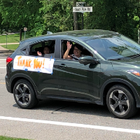 students waving from a car