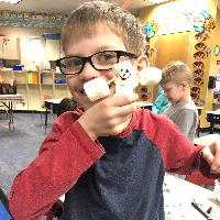 Student holding his marshmallow snowman