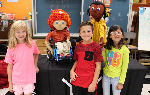 Three students with two of the puppets