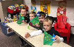 Four students with their origami Christmas trees