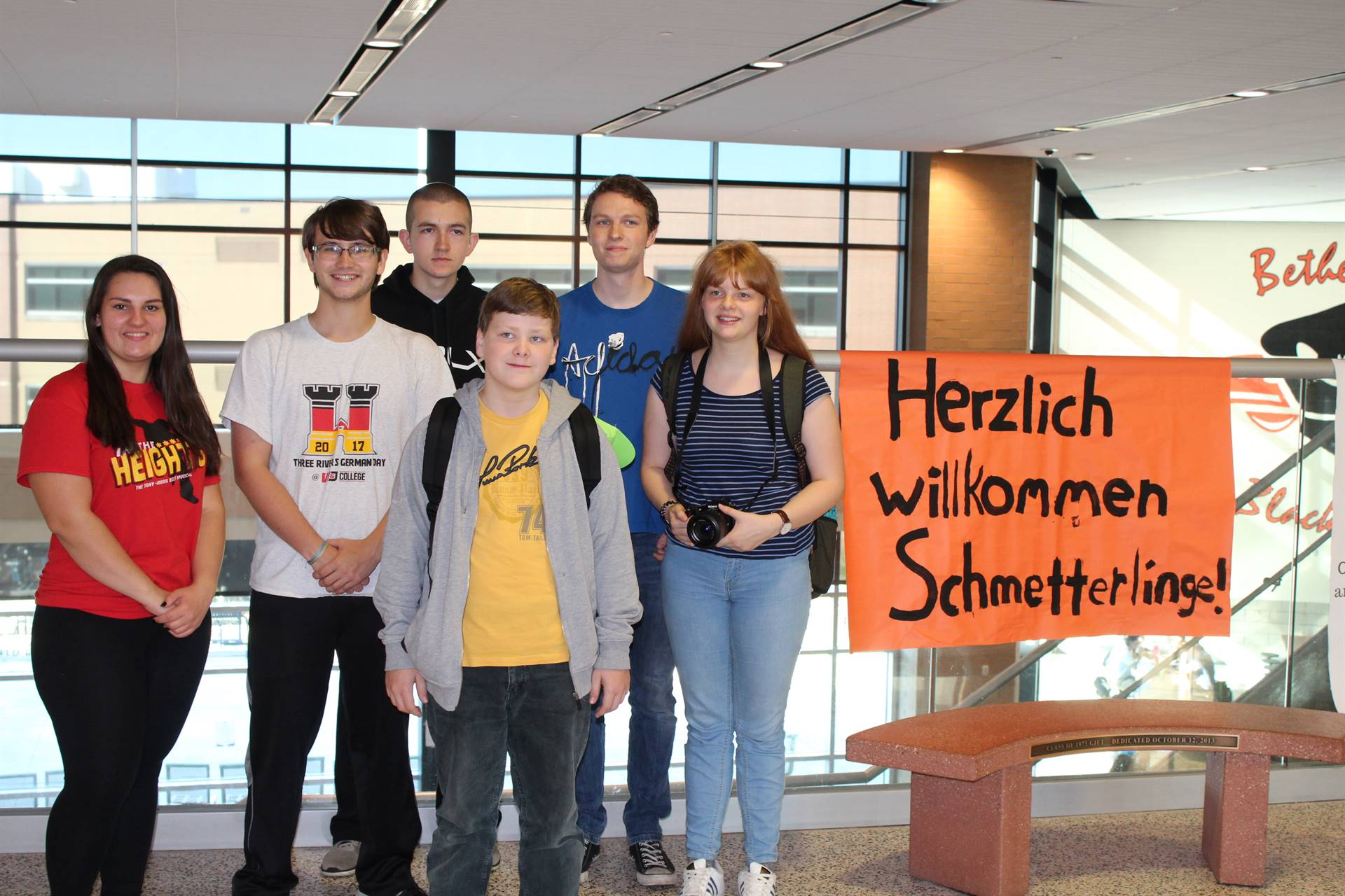 Students stand beside the welcome sign