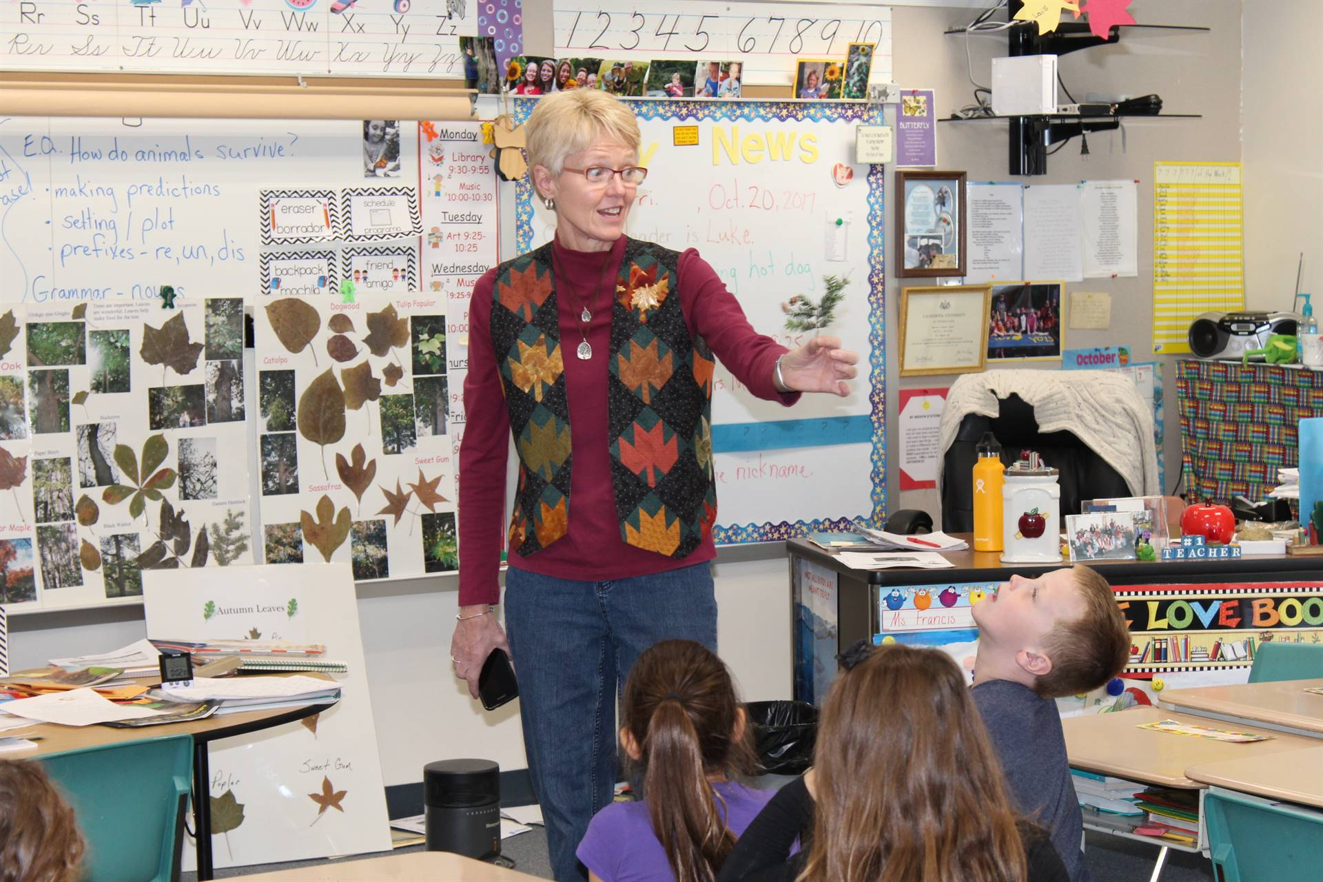 Ms. Francis holds up a leaf for students to identify