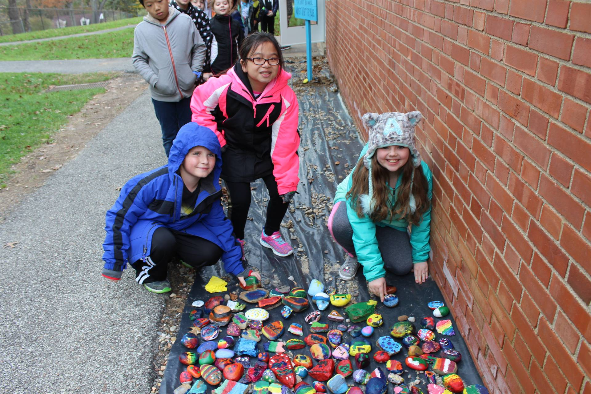 Students place their rocks in the rock garden